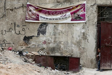 A girl looks out from a door near a poster advertising for a beauty salon in the rebel held Qaboun neighborhood of Damascus