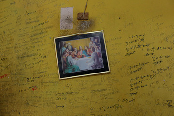 """Annotations with the record of the incomes and expenses of the house, are seen written on the wall next to an illustration depicting """"The Last Supper"""" in the house of Juan Pulgar, his daughter Zulay and their family in Punto Fijo"""