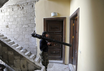A Free Syrian Army fighter watches Syrian Army positions before firing a B-10 recoilless gun in the Haresta neighbourhood of Damascus