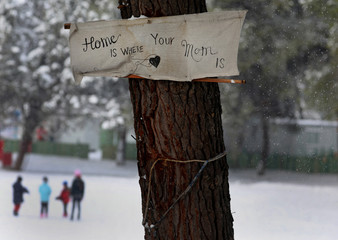 "A banner reading: ""Home is where your mom is"" is attached to a tree as stranded Syrian refugee children walk through a snowstorm at a refugee camp north of Athens"