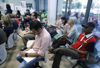 Job seekers wait inside a government-run employment office in Madrid