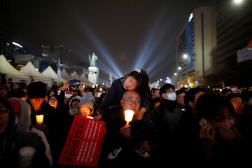 A girl rests on her father's shoulder as they march toward the Presidential Blue House during a protest calling South Korean President Park Geun-hye to step down in Seoul