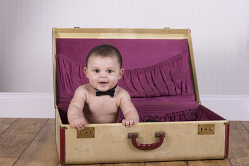 Adorable baby boy sitting in a suitcase