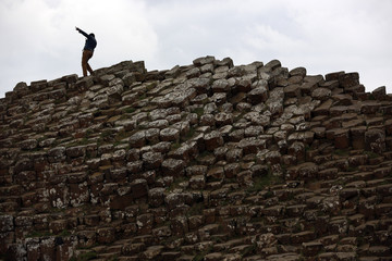 A man poses for a picture on the rocks at the Giant's Causeway situated on the north coast of Northern Ireland.