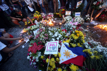 Mourners offer flowers and candles during a memorial service for victims of a blast at a market in Davao city