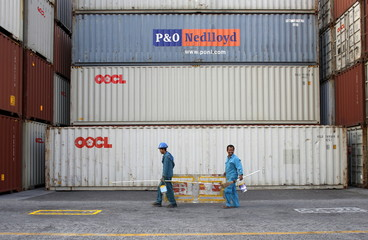 Workers walk near containers at Koja Container Terminal near Tanjung Priok port in Jakarta