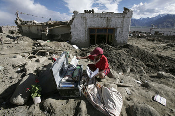 A flash flood victim checks his belongings outside his damaged house after flash floods occured on the outskirts of Leh, east of Srinagar
