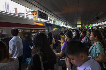 Passengers wait to board a skytrain during rush hour at a station in Bangkok