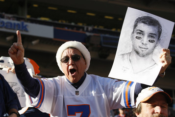 A fan of Denver Broncos' Tebow holds a drawing of him in the stands before their NFL football game against the New England Patriots in Denver