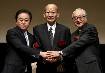 Japan Post Holdings Co President Nishimuro, Japan Post Bank Co President Nagato and Japan Post Insurance Co President Ishii pose for photos during joint news conference after ceremony to mark company's debut on Tokyo Stock Exchange