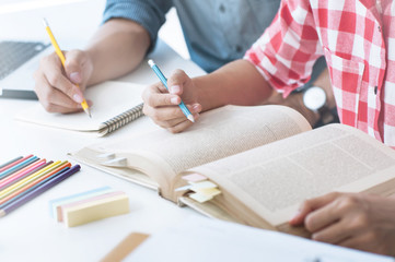 Two confident students reading a book or doing homework together while sitting at the home
