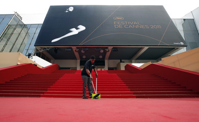A worker cleans the red carpet in front of the main entrance of the Festival Palace during the 64th Cannes Film Festival