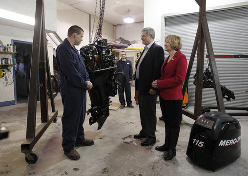 Conservative leader and Canada's PM Harper and his wife Laureen talk to mechanic Manning during a campaign stop at a marine equipment shop in Regina
