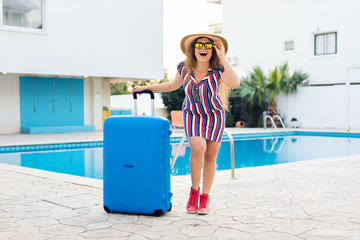 Happy young woman with blue luggage arriving to the resort. She is walking next to the swimming pool. Beginning of summer vacation concept.