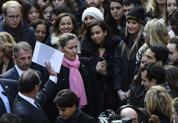 French President Francois Hollande stands among students after a minute of silence at the Sorbonne University in Paris to pay tribute to victims of Friday's Paris attacks