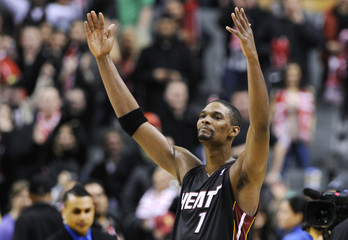 Miami Heat Chris Bosh waves to the crowd after his team defeated his former team the Toronto Raptors in their NBA basketball game in Toronto