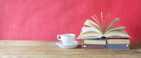 open book and cup of coffee on red background,free copy space