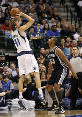 Dallas Mavericks forward Dirk Nowitzki shoots over San Antonio Spurs center Boris Diaw during their NBA basketball game in Dallas, Texas