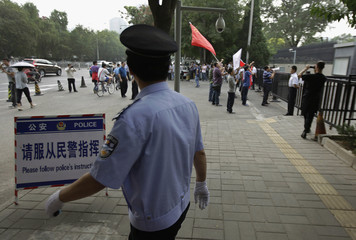 A policeman walks past a police notice board instructing media personel as demonstrators protest outside Japanese embassy in Beijing