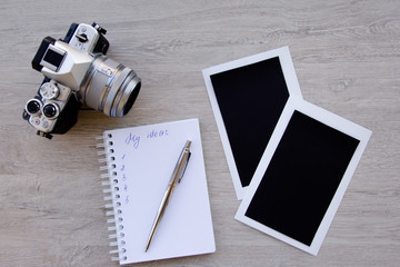 Blank photo frames, camera and supplies on wooden table. Top view. space for text