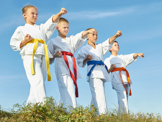 Against the background of the blue sky, children training blow hand