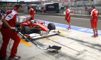 Ferrari Formula One driver Alonso of Spain simulates a pit stop during the second practice session for the Hungarian F1 Grand Prix near Budapest