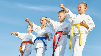 Children in karategi are training blow hand on blue sky background