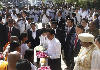 Japan's Prime Minister Abe and his wife Akie hold flowers as they preparing to participate for religious ceremony  at Kelaniya Buddhist Temple in Kelaniya