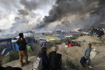 "Smoke rises the sky as migrants and journalists look at burning makeshift shelters and tents in the ""Jungle"" on the third day of their evacuation as part of the dismantlement of the camp called the ""Jungle"" in Calais"