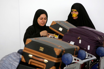 Women check their luggage after arriving on a flight from Dubai on Emirates Flight 203 at John F. Kennedy International Airport in Queens, New York, U.S.