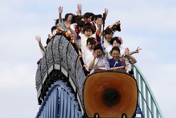 Japanese women wearing kimonos ride a roller coaster during their Coming of Age Day celebration ceremony at an amusement park in Tokyo