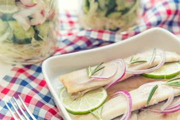 Sliced herring fillets, cut onion and lime