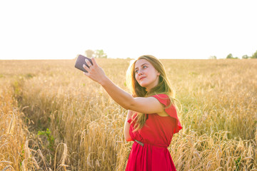 technology, summer holidays, vacation and people concept - smiling young woman taking selfie by smartphone on cereal field
