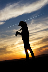 Silhouette Woman Photographing Landscape At Sunset. Female photographer holding a camera. Adventure concept at nature