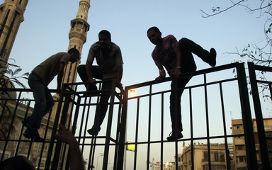Demonstrators climb over the fence of a hospital as they clash with loyalists of the ruling military council near the defence ministry in Cairo