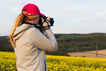 Young tourist woman photographing landscape with rape field. Woman taking pictures of the countryside.