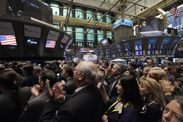 Traders and guests applaud during the ringing of the opening bell at the New York Stock Exchange