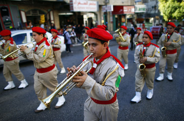 Members of a Palestinian boy scout marching band play their instruments during a rally in Bethlehem