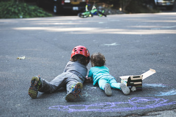 Small Children Coloring Pavement with Chalk