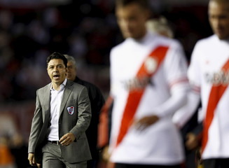 River Plate's head coach Gallardo talks to his players as they leave the pitch at halftime of their Copa Libertadores soccer match against Boca Juniors in Buenos Aires