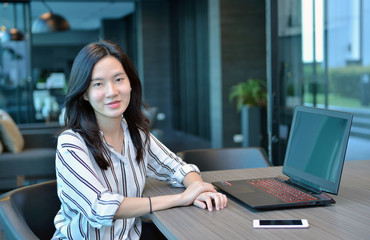 Casual Business Asian Woman smiling in front of a laptop in condo