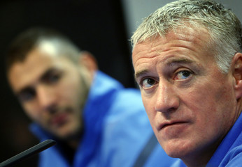 France's Benzema and his coach Deschamps look on during their news conference in Madrid