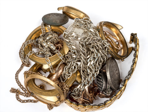 A scrap of precious metals. Old and broken jewelry, watches of gold and silver on a white background.