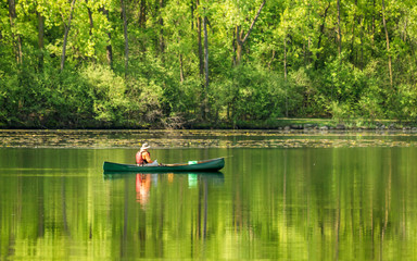 A man is canoeing on a lake at spring sunny day
