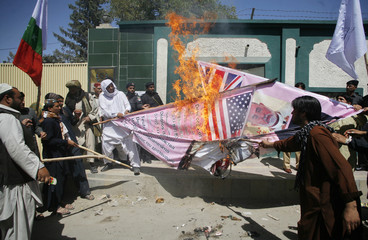 Supporters of Awami Majlis-e-Amal Pakistan burn banners representing the U.S. during a rally in Quetta