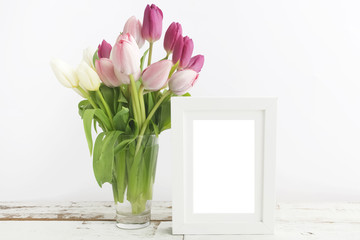 Tulip with blank picture frame on white wooden table