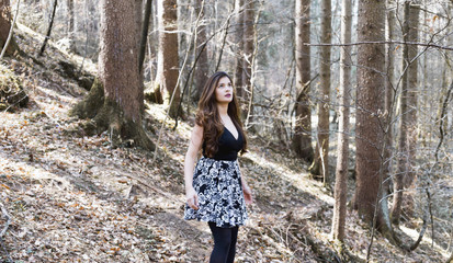 Portrait of beautiful woman in a forest, she is looking towards the sky