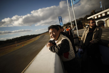 """Yamauchi smiles as he watches a John Player Special - Lotus 98t during the international presentation of the new Sony PlayStation """"Gran Turismo 6"""" video game in Ronda"""