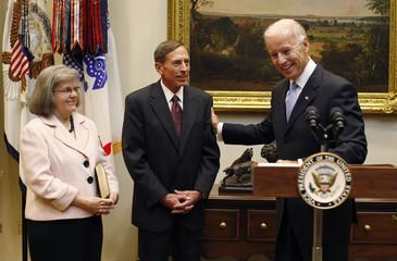 U.S. Vice President Joe Biden smiles before swearing-in David Petraeus as the new CIA Director, as Petraeus' wife Holly looks on in Washington