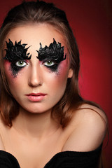 Girl with paper zigzag make-up and brown hair.Creative makeup.Red background